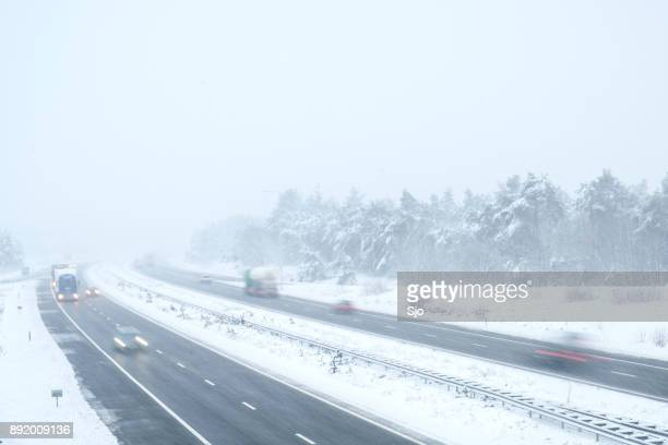 Traffic on a highway during a snow blizzard in winter