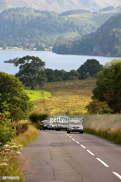 Traffic on a narrow country road in the English Lake District with Ullswater in the background