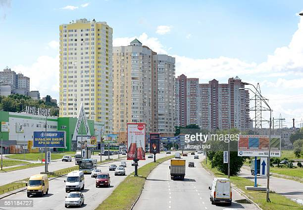 Traffic on a road on the outskirts of Kiev with new apartment blocks in the background
