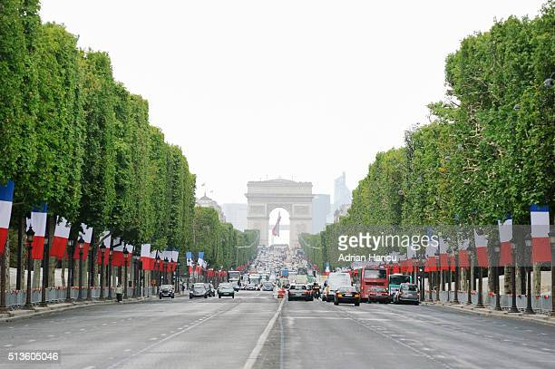 Traffic on Avenue des Champs-Elysees decorated with flags before the Bastille Day, Paris, France