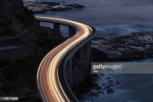 traffic on bridge - illuminated stock pictures, royalty-free photos & images
