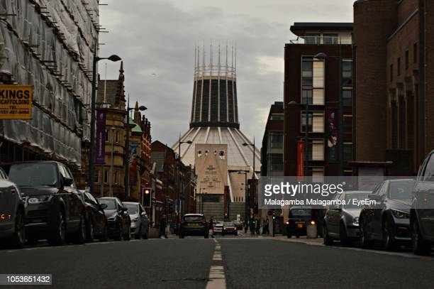 traffic on city street by buildings against sky - merseyside stock pictures, royalty-free photos & images
