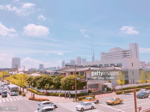 traffic on city street by buildings against sky - fukuoka city stock pictures, royalty-free photos & images