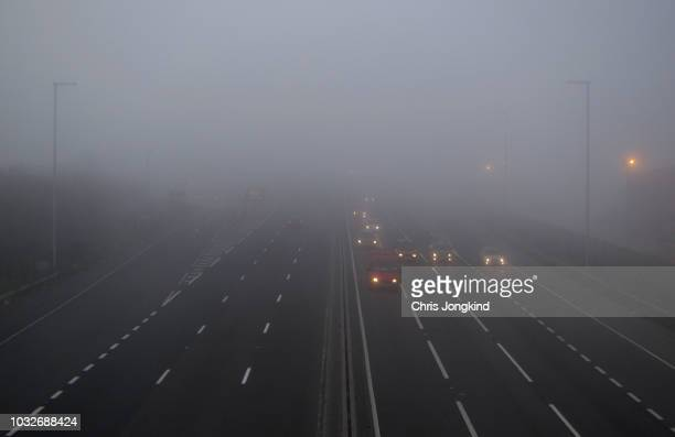 traffic on foggy expressway - mist stockfoto's en -beelden