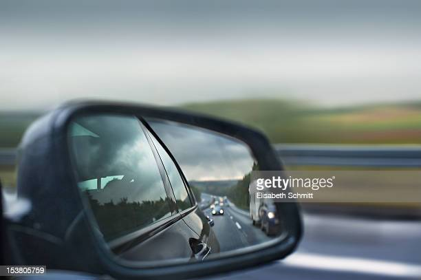 Traffic on highway visible in rear-view mirror