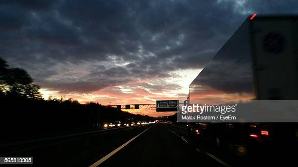 Traffic On Road Against Dramatic Sky At Dusk