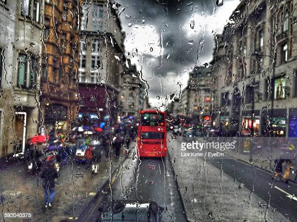 Traffic On Road Amidst Buildings Seen Through Wet Glass Window On Rainy Day