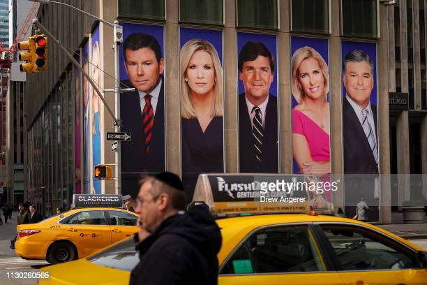 Traffic on Sixth Avenue passes by advertisements featuring Fox News personalities including Bret Baier Martha MacCallum Tucker Carlson Laura Ingraham...