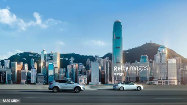 Traffic on street against Hong Kong cityscape with clear blue sky