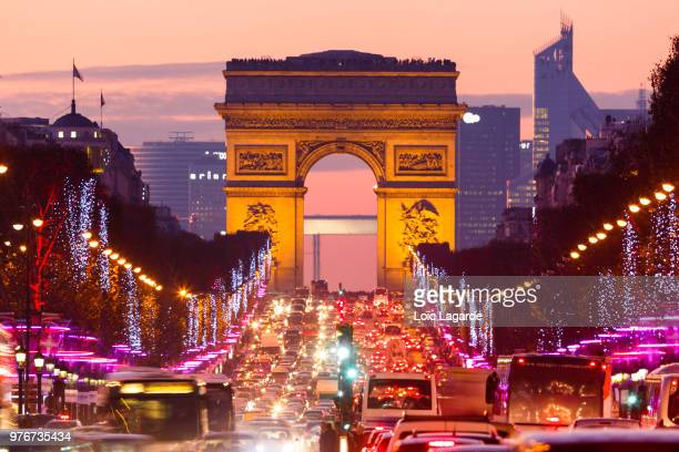 traffic on street at dusk, paris, france - place charles de gaulle paris stock photos and pictures
