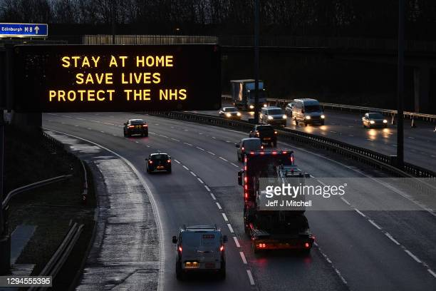 Traffic on the M8 motorway passes a road sign advising motorists to stay at home as Scotland enters a third Coronavirus lockdown on January 5, 2021...