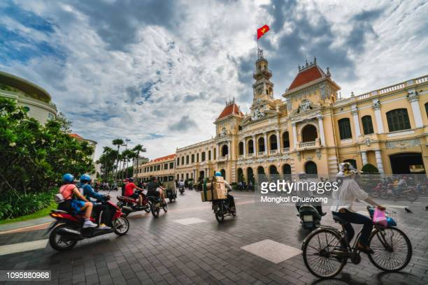 traffic on the road at front of ho chi minh city hall in ho chi minh city capital of vietnam - people's committee building ho chi minh city stock pictures, royalty-free photos & images