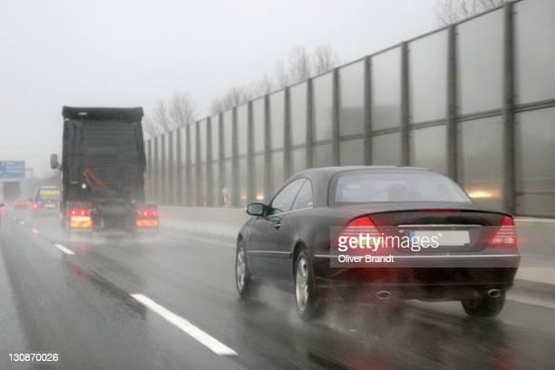 traffic on wet freeway, danger of aquaplaning - avenida fotografías e imágenes de stock