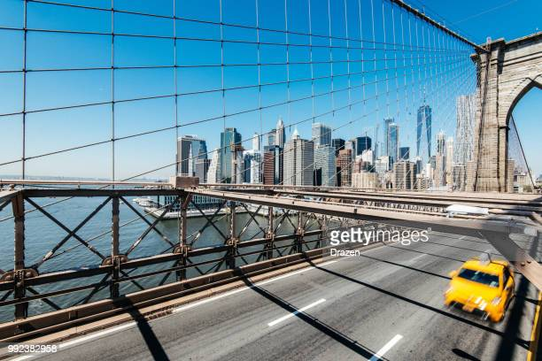 traffic over brooklyn bridge with manhattan in background - lower manhattan stock pictures, royalty-free photos & images