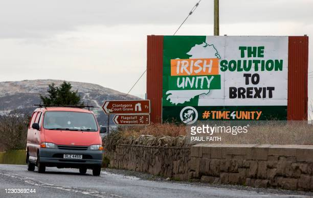 Traffic passes a billboard for Irish unification outside Newry, Northern Ireland near the border with Ireland on December 31, 2020. - Britain cuts...