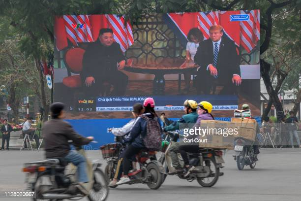 Traffic passes a large LED screen as it shows a handshake between US President Donald Trump and North Korean leader Kim Jongun on the second day of...
