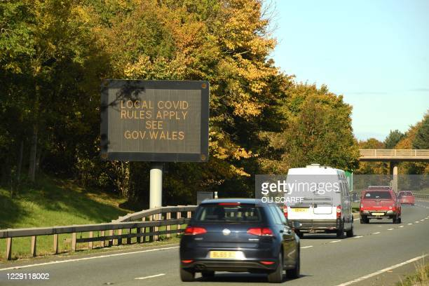 Traffic passes a 'local COVID-19 rules apply' sign displayed along the A55 near Mold in Flintshire, Wales on October 17 as further restrictions come...