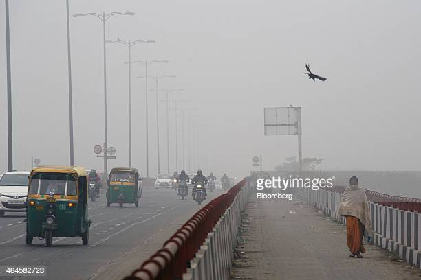 Traffic passes a pedestrian while traveling along a road shrouded in haze in New Delhi India on Monday Jan 20 2014 India China and Brazil three of...