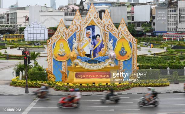 Traffic passes a portrait of Queen Sirikit and her son King Maha Vajiralongkorn during a public holiday on August 13 2018 in Bangkok Thailand The...
