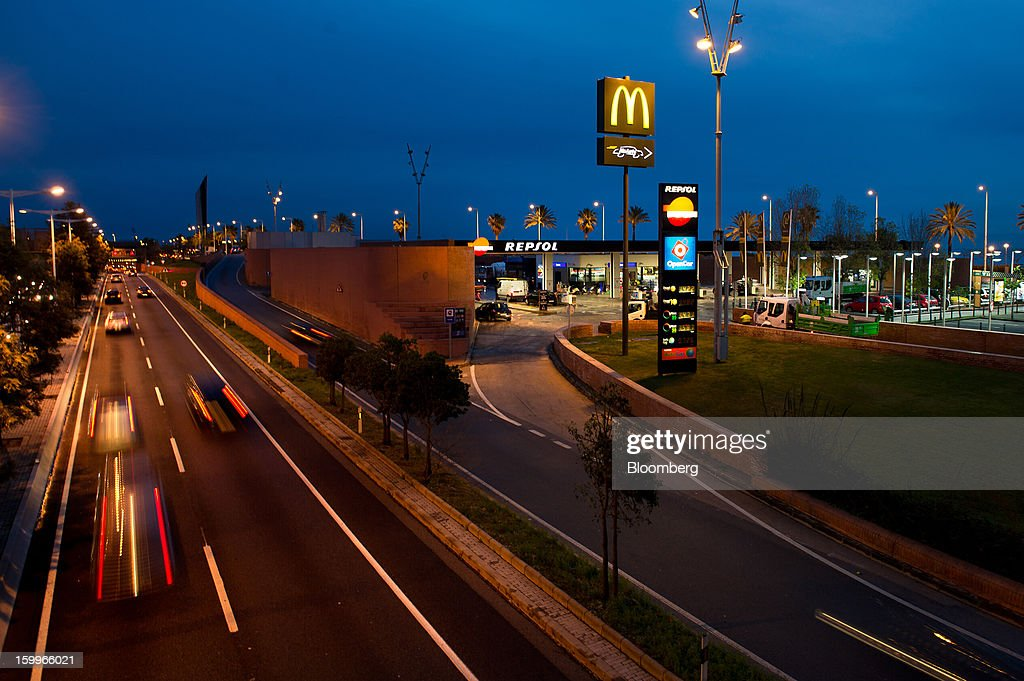 Traffic passes a Repsol SA gas station illuminated at night beside a highway in Barcelona, Spain, on Wednesday, Jan. 23, 2013. Repsol SA, Spain's largest energy company, expects to sell liquefied natural gas assets for about 2 billion euros ($2.7 billion) by early February, according to a person familiar with the matter. Photographer: David Ramos/Bloomberg via Getty Images