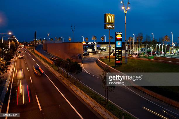 Traffic passes a Repsol SA gas station illuminated at night beside a highway in Barcelona Spain on Wednesday Jan 23 2013 Repsol SA Spain's largest...