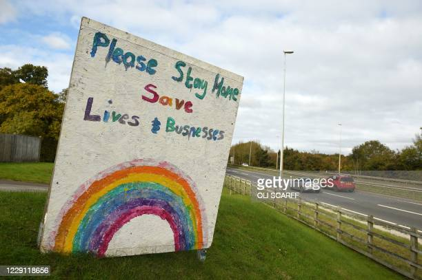 """Traffic passes a sign asking people to """"stay home"""" outside a pub in Flint in north Wales on October 17 as further restrictions come into force as the..."""