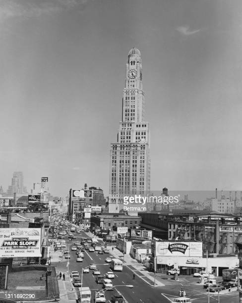 Traffic passes along Flatbush Avenue with the Williamsburgh Savings Bank Tower rising in the Brooklyn borough of New York City, New York, circa 1965....
