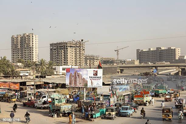 Traffic passes an advertisement billboard for residential project displays as buildings stand under construction in the background in Karachi...