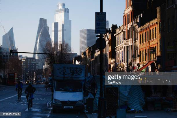 Traffic passes beside market stalls in Whitechapel as the towers of the Leadenhall Building , 30 St Mary Axe , and 22 Bishopsgate stand in winter...