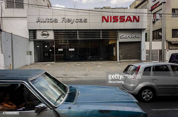 Traffic passes by a closed Nissan Motor Co dealership in the Altamira section of Caracas Venezuela on Friday Feb 28 2014 Antigovernment protests have...