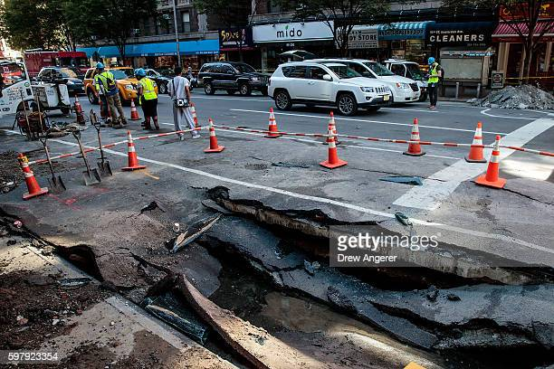 Traffic passes by a sinkhole caused by a water main break on Amsterdam Avenue, in the Upper West Side section of Manhatten, August 30, 2016 in New...