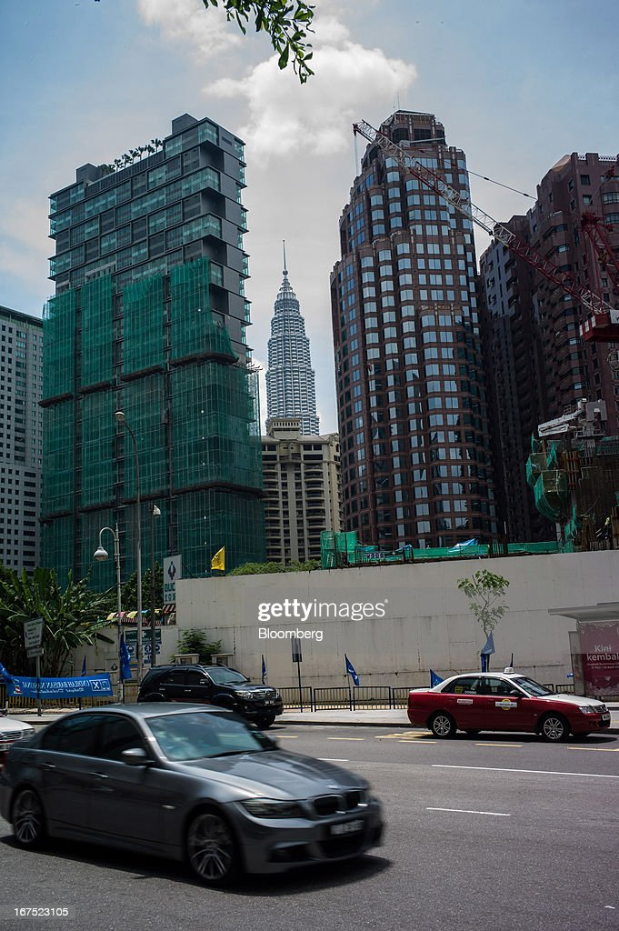 Traffic passes by buildings under construction as one the Petronas Twin Towers is seen in the background, center, in Kuala Lumpur, Malaysia, on Thursday, April 25, 2013. Malaysians will go to the polls on May 5. Prime Minister Najib Razak's National Front coalition is seeking to extend its 55 years of unbroken rule in the face of a resurgent opposition led by Anwar Ibrahim. Photographer: Sanjit Das/Bloomberg via Getty Images