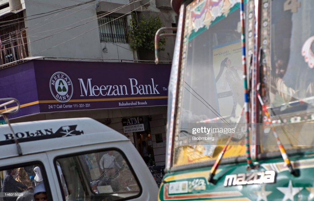 Traffic passes in front of a branch of the Meezan Bank Ltd  in