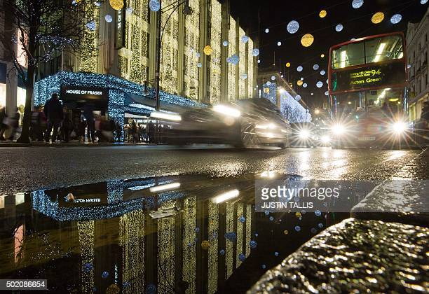 Traffic passes stores bedecked with Christmas lights on Oxford Street in central London on December 20 on the final shopping Sunday before Christmas...