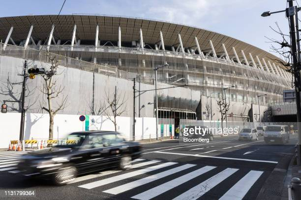 Traffic passes the construction site of the New National Stadium the main venue for the Tokyo 2020 Olympic and Paralympic Games in Tokyo Japan on...
