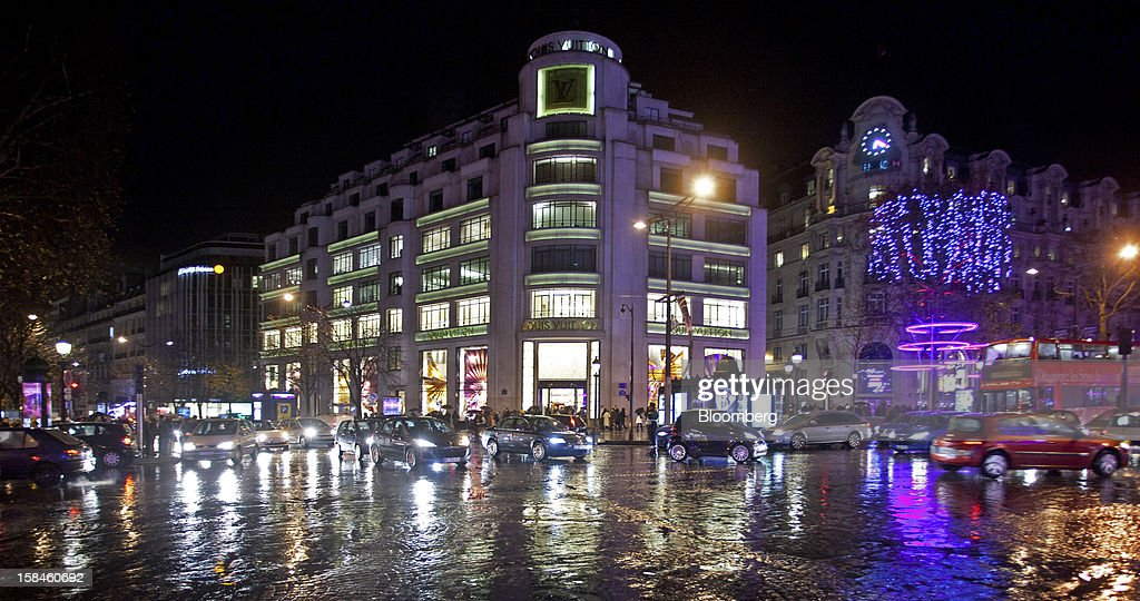 Traffic passes the illuminated Louis Vuitton store, operated by LVMH Moet Hennessy Louis Vuitton SA, on the Champs-Elysees in Paris, France, on Saturday, Dec. 15, 2012. The French minister for energy and environment unveiled a proposal for lights in and outside shops, offices, and public buildings -- including the flagship Louis Vuitton store and the Lido cabaret house on Paris's Avenue des Champs Elysees -- to be turned off between 1 a.m. and 7 a.m. starting in July. Photographer: Balint Porneczi/Bloomberg via Getty Images