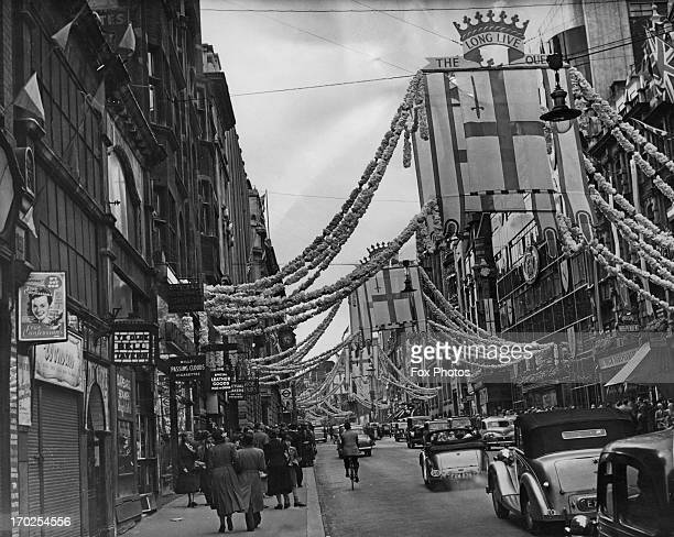 Traffic passes underneath the Coronation decorations in Fleet Street London June 1953