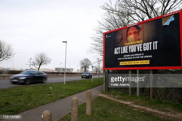 Traffic passing a coronavirus billboard in view of Heathrow Airport on February 13, 2021 in London, England. From 15 February travellers to the UK...