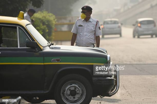 A traffic police constable wears a mask during a clean air campaign on October 25 2017 in New Delhi India
