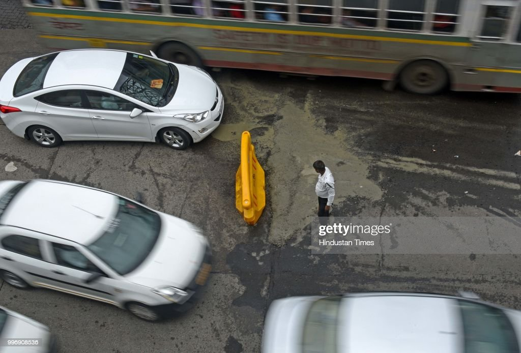A traffic police cover the Potholes on WEH near Thakur village, Kandivali, on July 11, 2018 in Mumbai, India. Heavy rains made a comeback in Mumbai causing waterlogging in many parts of the city leading to disruptions in traffic services and affected local train services. The India Meteorological Departments (IMD) Mumbai office has said heavy rainfall will continue in some parts of the city and its suburbs after similar conditions over the weekend.