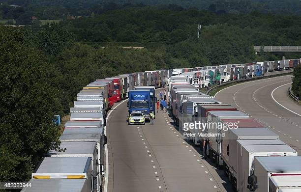 Traffic police escort a trick truck on the M20 motorway during Operation Stack on July 30 2015 near Charing England Operation stack remains in place...
