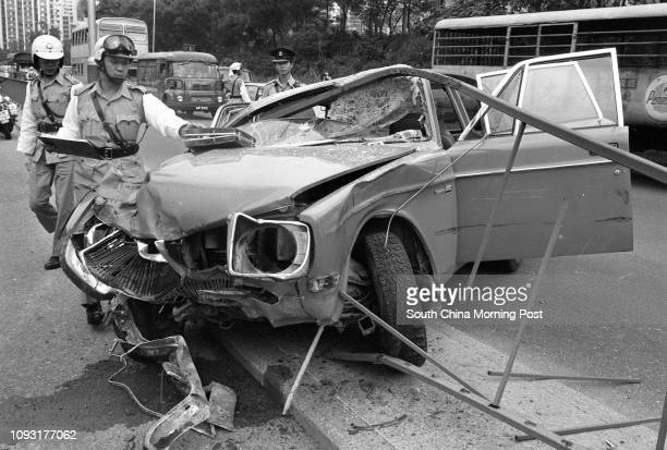 Traffic police examining the damage of a car which crashed into the central divider of Waterfront Road near Victoria Park 19OCT78