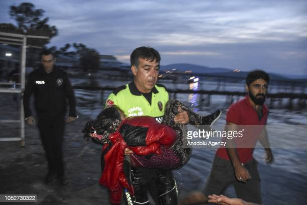 A traffic police officer carries a migrant girl who barely escaped drowning to the ambulance as Turkish Coast Guards conduct a search and rescue...
