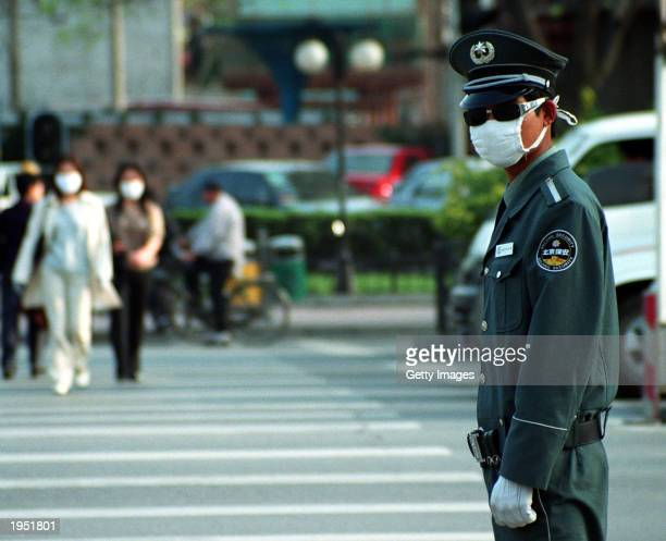 Traffic police officer on duty at an intersection in the Jianguomenwai district wears a face mask for protection from SARS April 25,2003 in Beijing,...