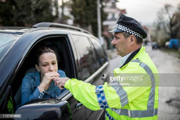 traffic police officer stopped woman for alcohol test - drinking and driving stock photos and pictures