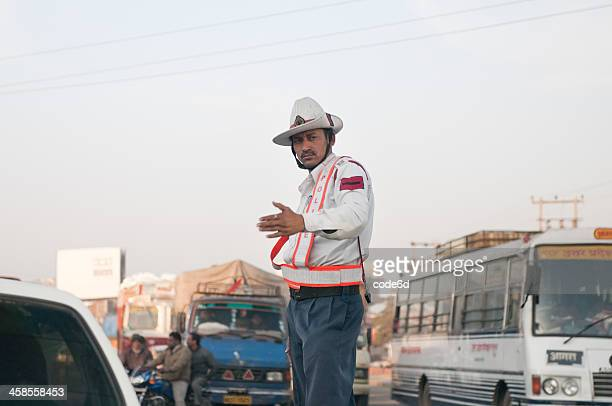 traffic police officer waving at cars in haryana, india - traffic cop stock pictures, royalty-free photos & images