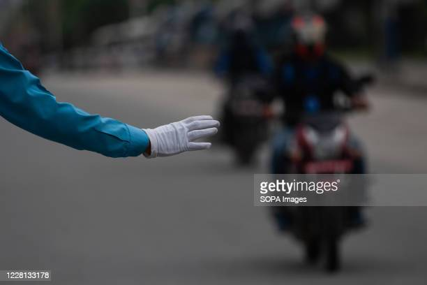 Traffic police officer wearing a surgical hand glove stands on guard on a deserted road during the first day of the prohibitory order. Kathmandu...