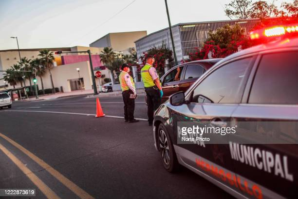 Traffic police officers stand at a checkpoint on Rosales Boulevard to check if car drivers comply with the measures to prevent the spread of COVID-19...