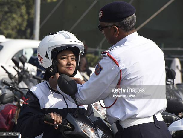 A traffic police official helps a participant to wear a helmet during the culmination function of National Road Safety Week 2017 to educate commuters...