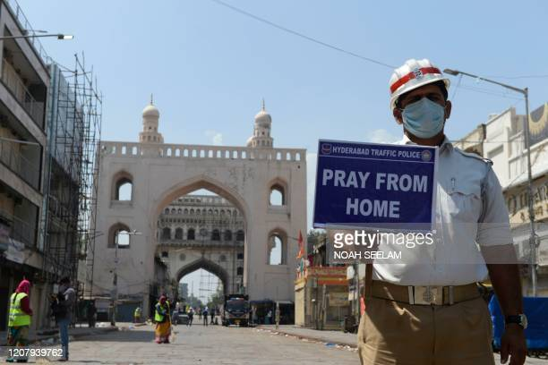 Traffic police personnel holds a placard on a deserted road during a one-day nationwide Janata curfew imposed as a preventive measure against the...